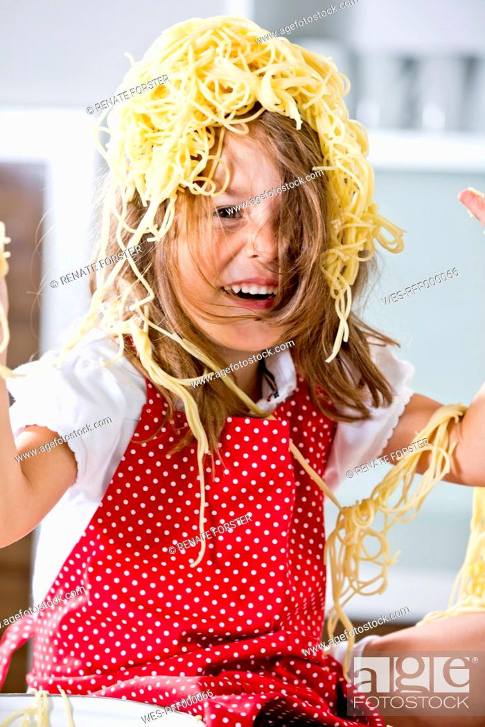 Stock Photo: Germany, Girl playing with spaghetti.