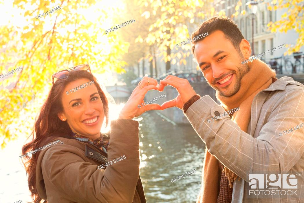 Imagen: Portrait smiling young couple forming heart-shape with hands at sunny autumn canal.