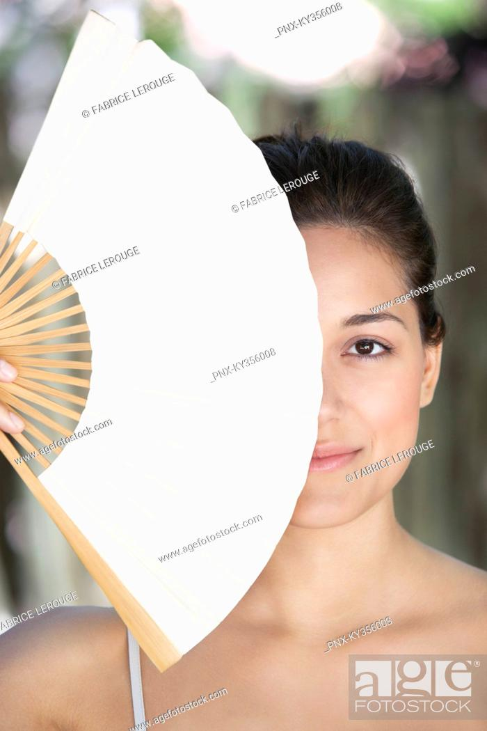 Stock Photo: Beautiful young woman holding a Chinese fan in front of her face.