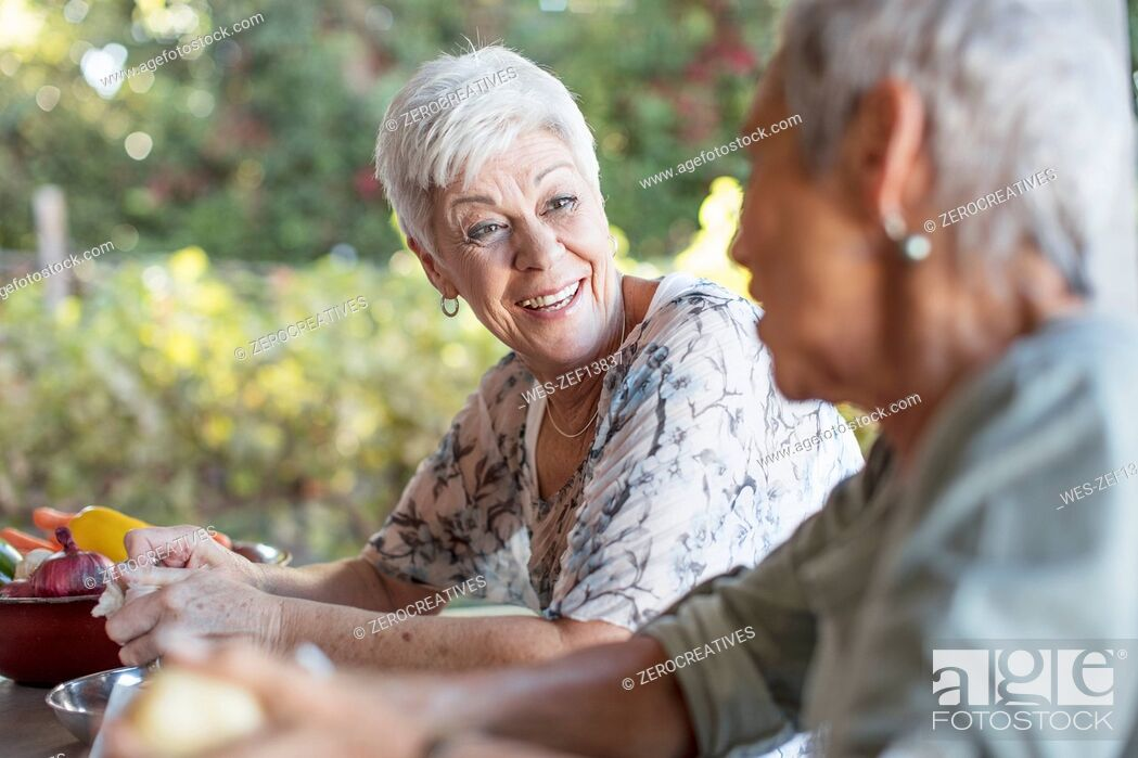 Stock Photo: Portrait of smiling senior woman listening to her friend on terrace while preparing lunch.