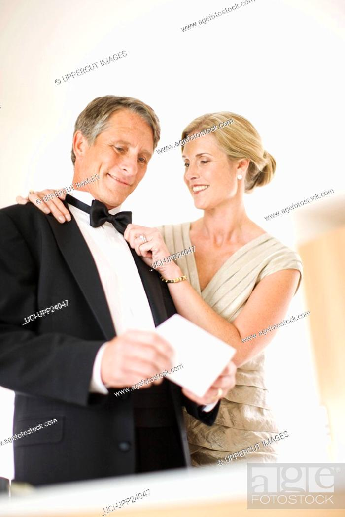 Stock Photo: Couple in eveningwear holding wedding invitation.