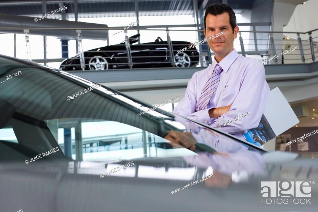 Stock Photo: Car salesman standing beside new saloon cars in showroom, holding brochure, smiling, portrait.