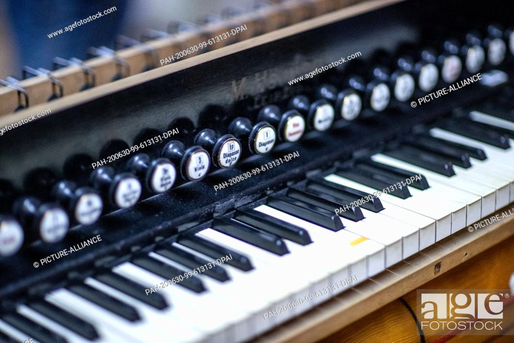 "Stock Photo: 22 June 2020, Mecklenburg-Western Pomerania, Rostock: The keyboard of a harmonium from the 1930s is restored in the workshop """"Historical Keyboard Instruments -."