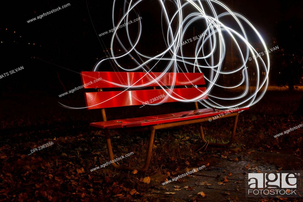 Stock Photo: A red park bench in autumn with swirls of white light in the sky around it; Locarno, Ticino, Switzerland.