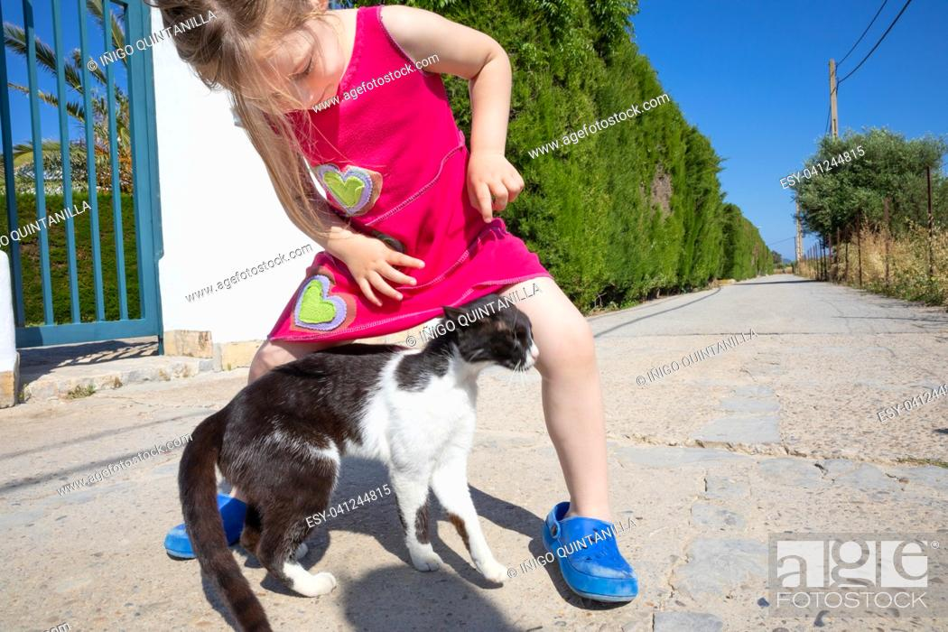 Stock Photo: white and black cat caressing little girl leg on the street, five years old child with pink dress, in Summertime.