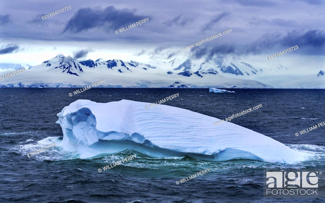 Imagen: Floating Blue Iceberg Glaciers Snow Mountains Sea Water Charlotte Bay Antarctic Peninsula Antarctica. Glacier ice blue because air squeezed out of snow.