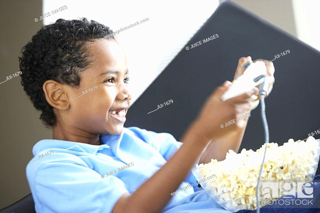 Stock Photo: Boy 7-9 wearing blue polo shirt, playing on games console at home, bowl of popcorn in lap, smiling, side view, close-up.