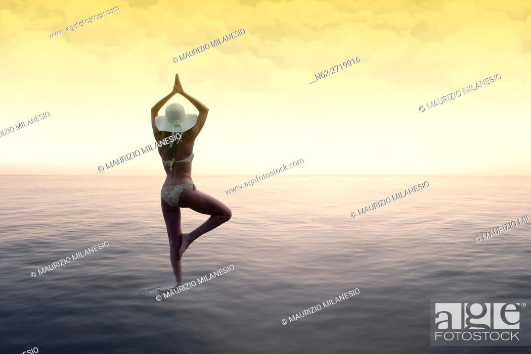 Stock Photo: Woman with a white hat standing on the water in the sun salutation yoga pose, on background sky with colored clouds by a warm sunset.