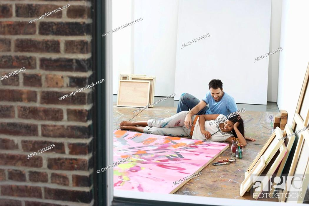 Stock Photo: Couple reclining by painting on floor of studio view through window.