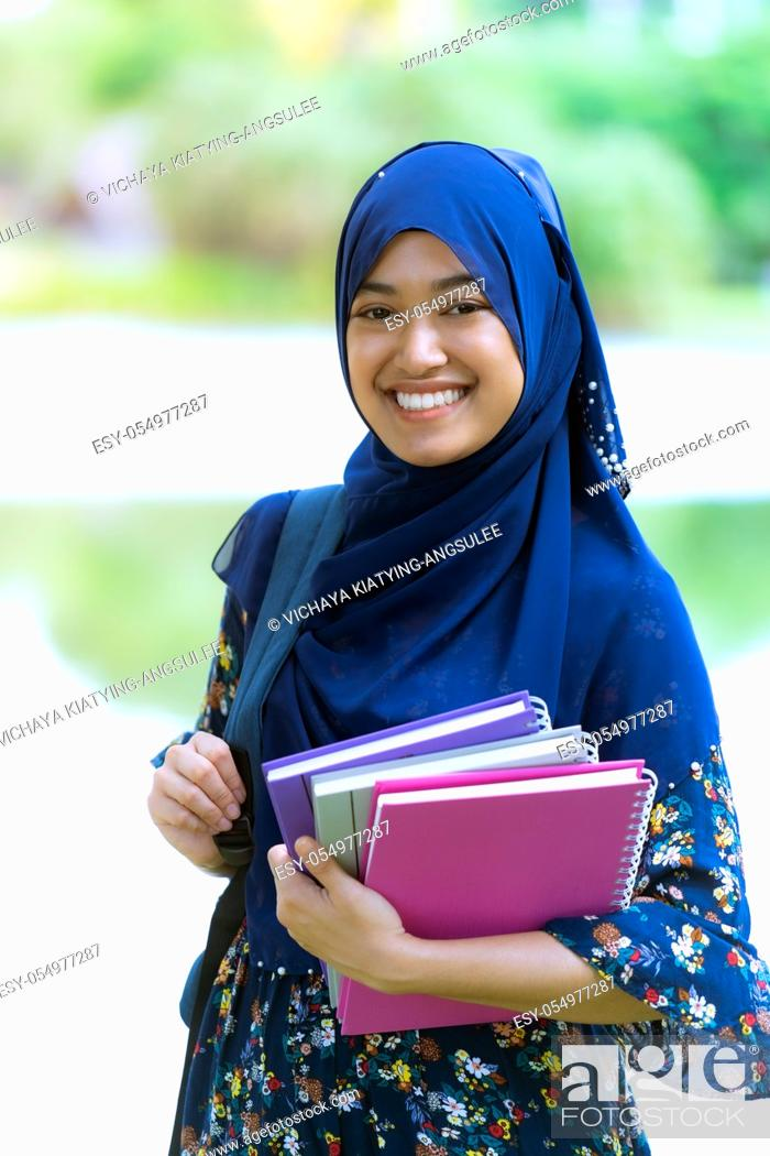 Stock Photo: Portrait of good-looking Happy young teenager Muslim islamic asian university girl holding hers books for knowledge and wisdom concept.