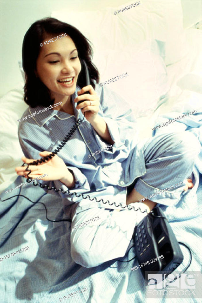 Stock Photo: High angle view of a young woman sitting on a bed talking on a telephone.