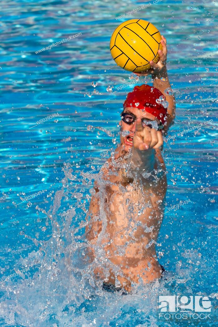 Stock Photo: Water Polo player jumps high in pool to shoot for goal.