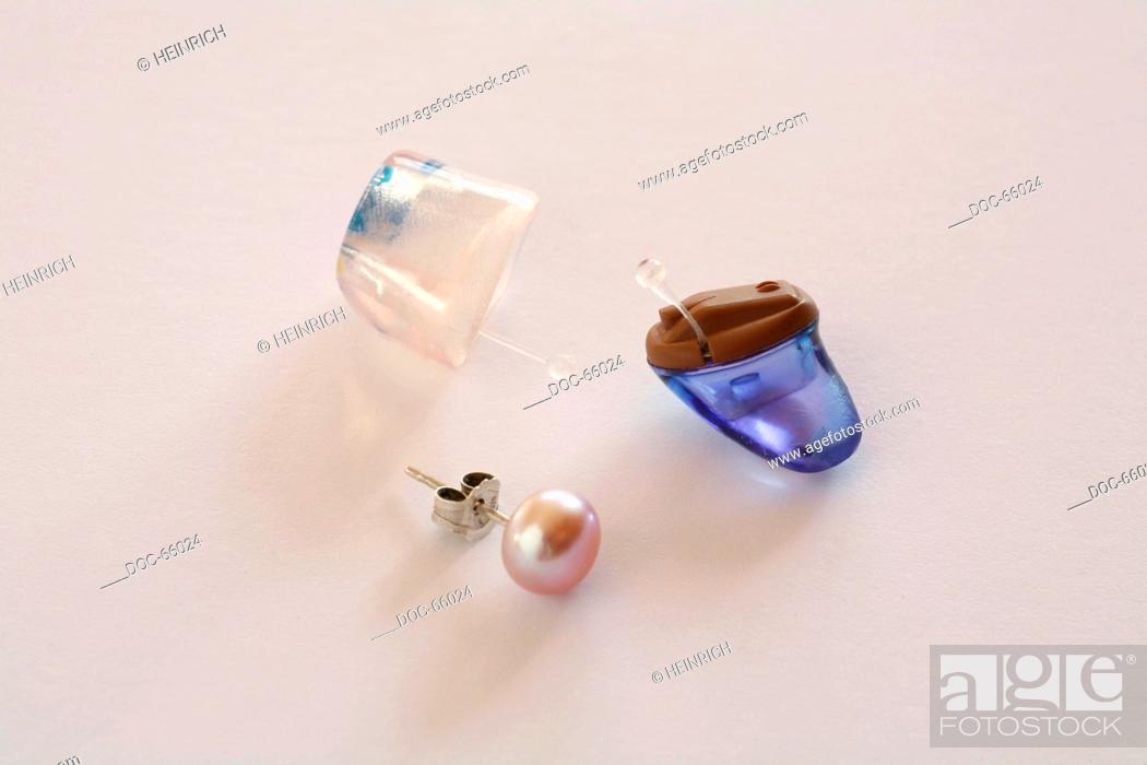 Imagen: on-white - two different hearing aids and one earring - acoustic hearing apparatus - hearing device.