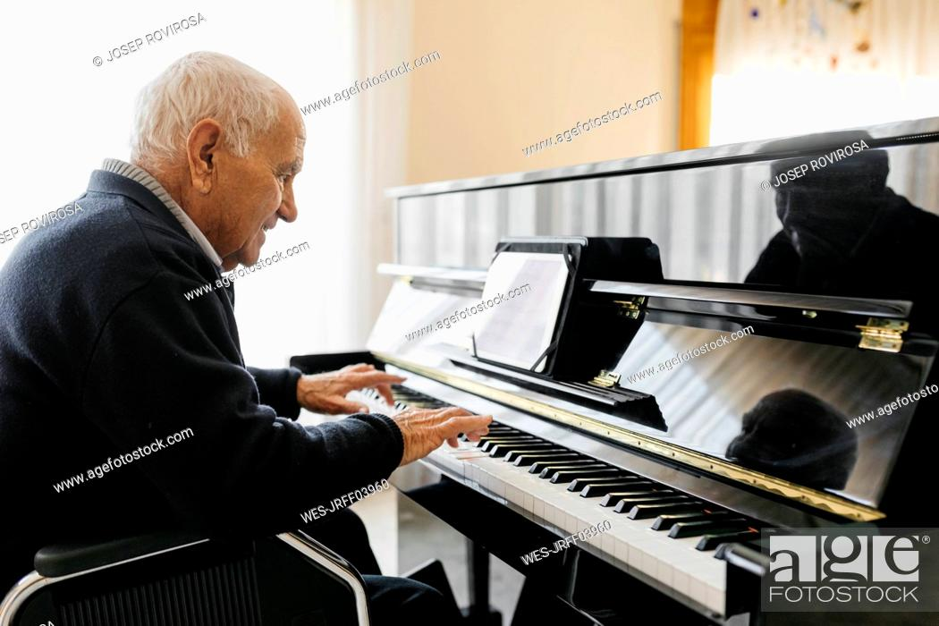 Imagen: Senior man sitting in wheelchair playing piano at home.