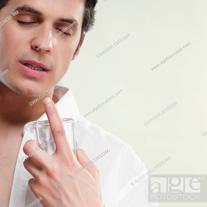 Imagen: Close-up of a man smelling perfume.