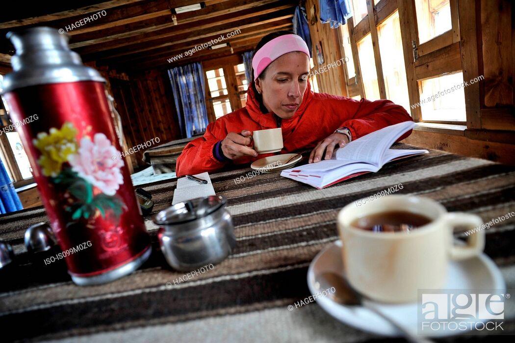Stock Photo: Woman reading guidebook at teahouse, Yak Kharka, Nepal.