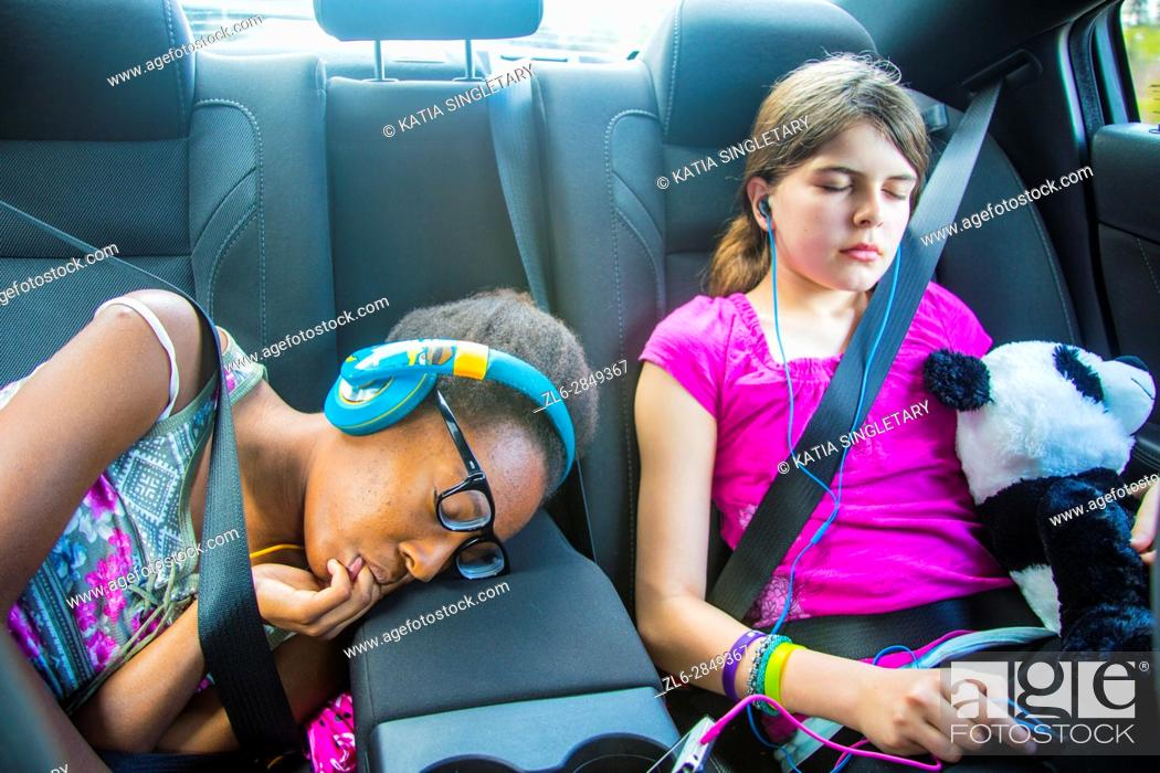 Stock Photo: 2 girls, one caucasian preteen and one african american teen sucking her fingers in the car sleeping and resting with stuff animals and earphones on.