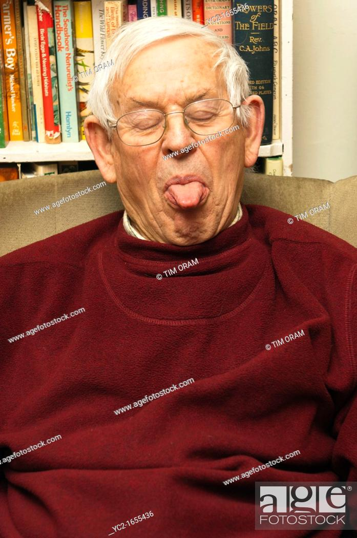 Stock Photo: A senior elderly man in his 80's pulling a funny face at home in England , Britain , Uk.