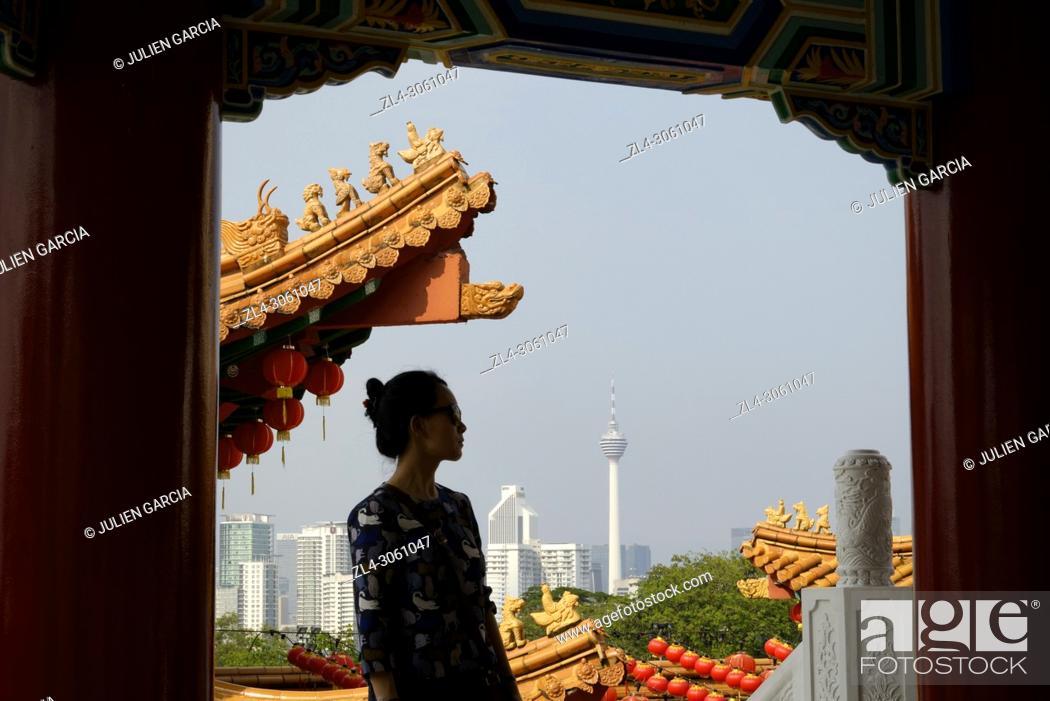 Stock Photo: Malaysia, Selangor State, Kuala Lumpur, woman at Thean Hou Chinese Temple, KL tower (Menara Kuala Lumpur) in the background, Model Released.