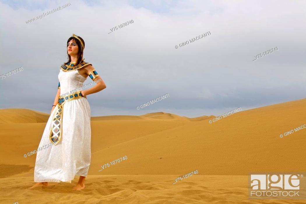 Stock Photo: Girl dressed like Cleopatra posing on the desert dunes.