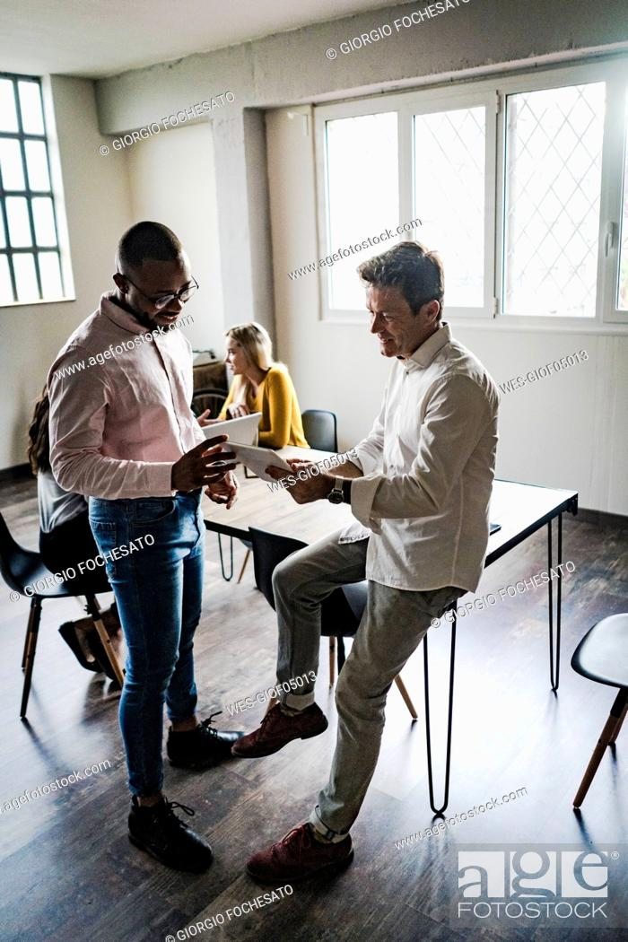 Stock Photo: Business team with tablets having a meeting in loft office.