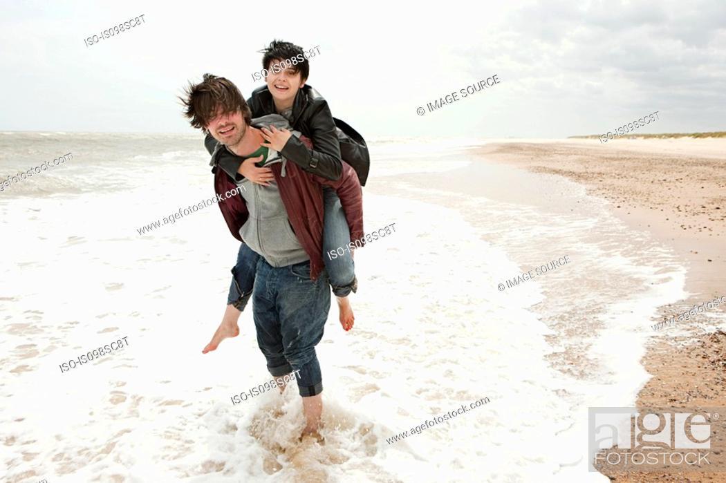 Stock Photo: man giving girlfriend piggyback in the sea.
