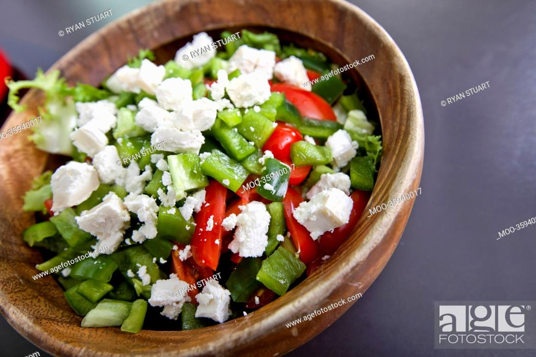 Stock Photo: Close-up of vegetable salad in wooden bowl on counter.