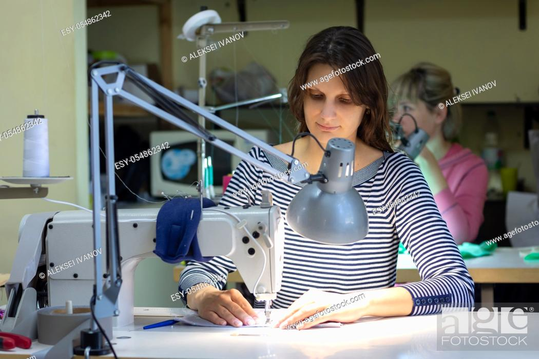 Stock Photo: a seamstress works behind a sewing machine in a sewing shop at her workplace.