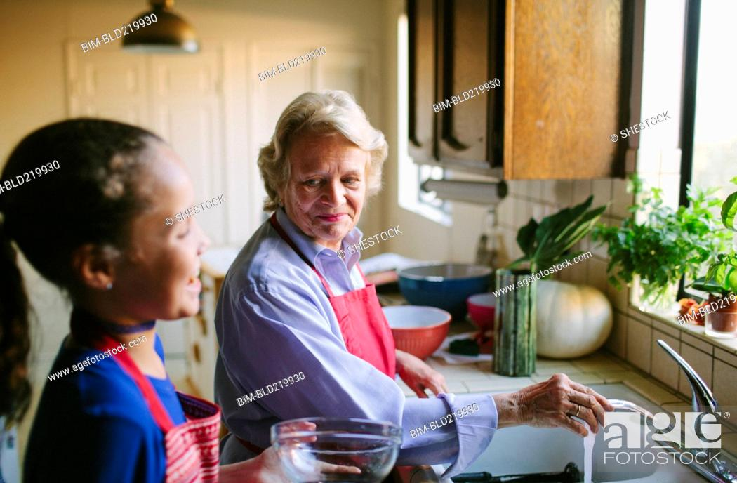 Stock Photo: Grandmother and granddaughter washing bowl in kitchen sink.
