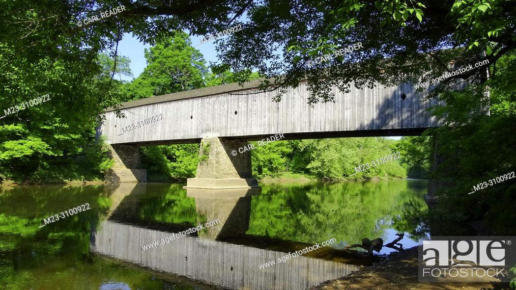Imagen: An old wooden covered bridge surrounded by summer foliage, Pennsylvania, USA.
