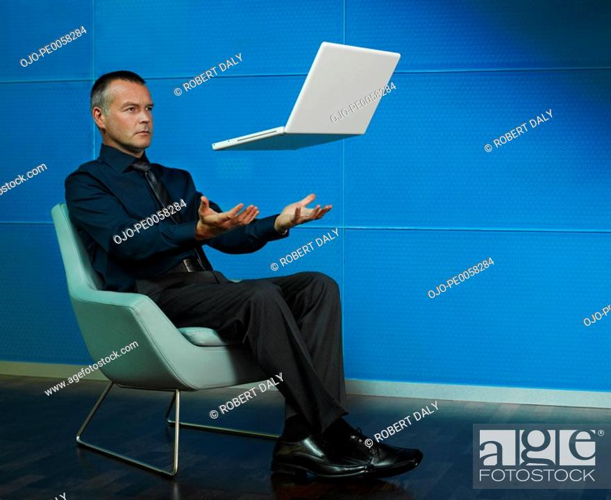 Stock Photo: Man sitting with laptop floating over his lap.