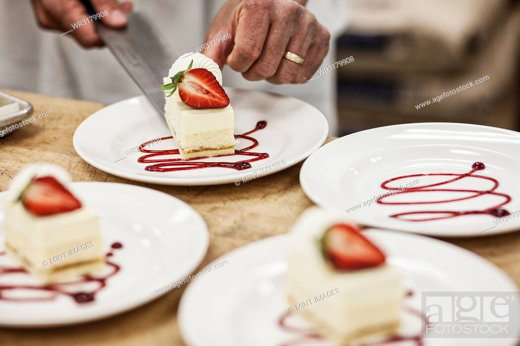 Stock Photo: Chef hands placing a layered desert on a plate, presentation of a sweet dish.