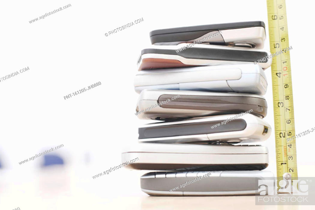 Stock Photo: Close-up of stack of mobile phones with a tape measure.