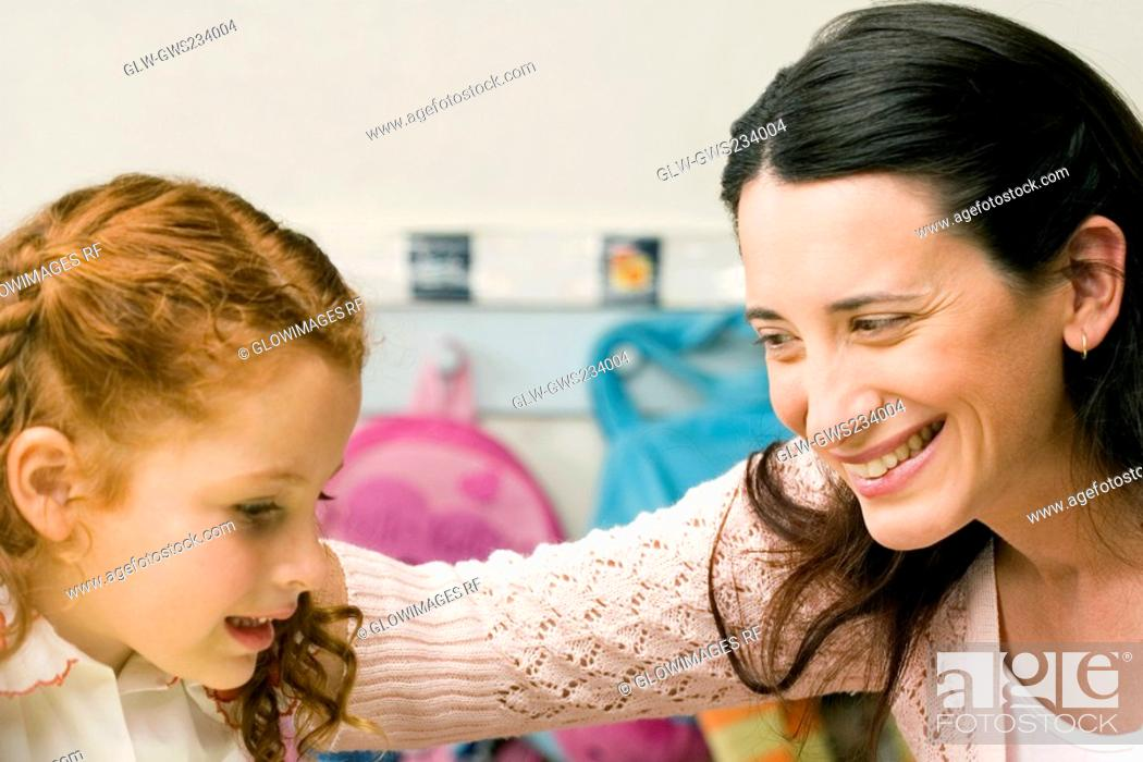 Stock Photo: Female teacher teaching her student in a classroom.