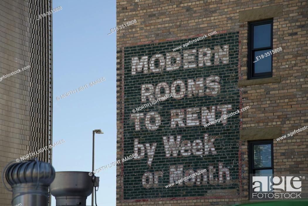 Stock Photo: Canada, Alberta, Calgary. Old fashioned sign painted on the side of brick building, advertising rooms to rent.