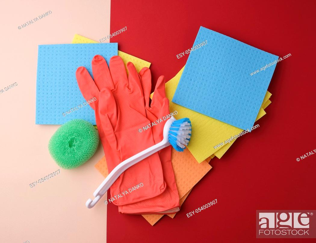 Stock Photo: items for home cleaning: red rubber gloves, brush, multi-colored sponges for dusting on a colored background, top view, flat lay.