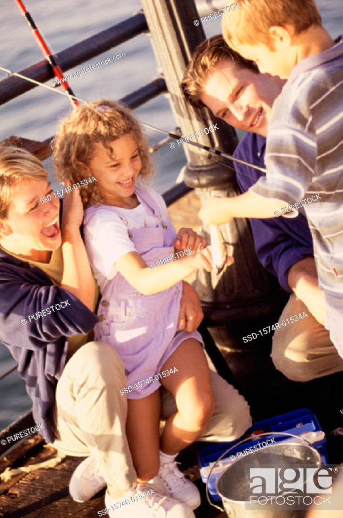 Stock Photo: Couple in a fishing boat with their son and daughter.