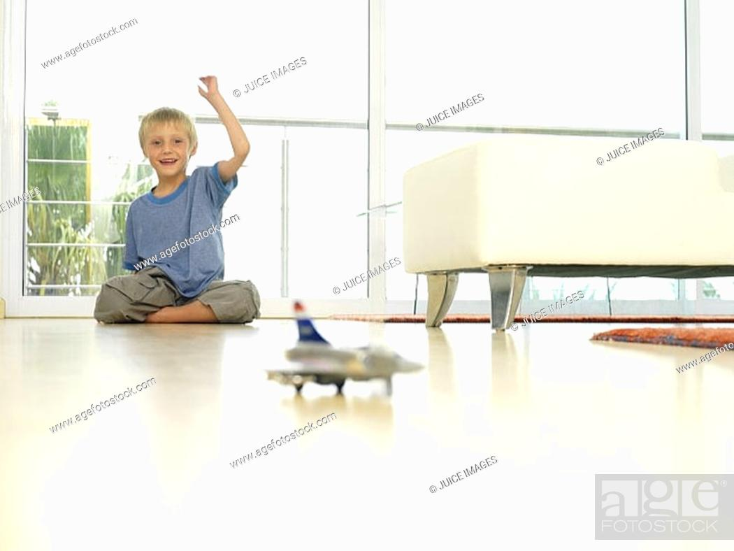 Stock Photo: Boy 5-7 playing with toy plane at home, sitting on floor with hand raised, smiling, surface level.