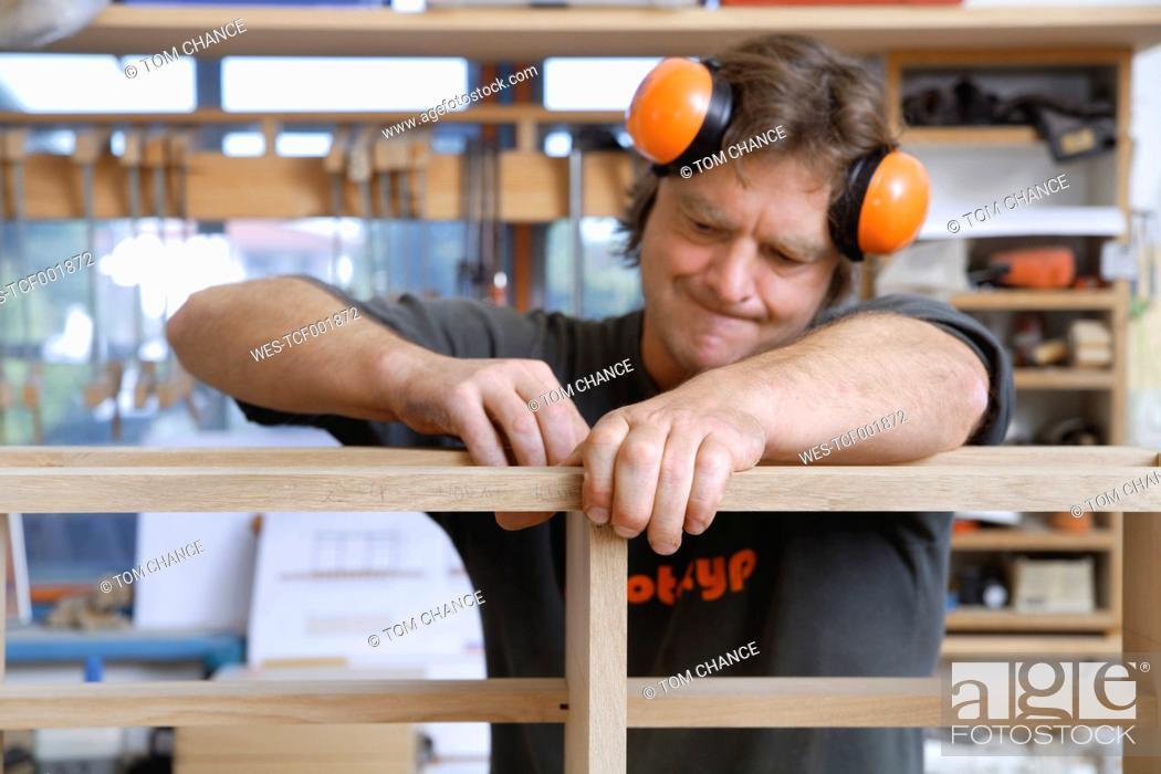 Stock Photo: Germany, Upper Bavaria, Schaeftlarn, Carpenter fixing wood.