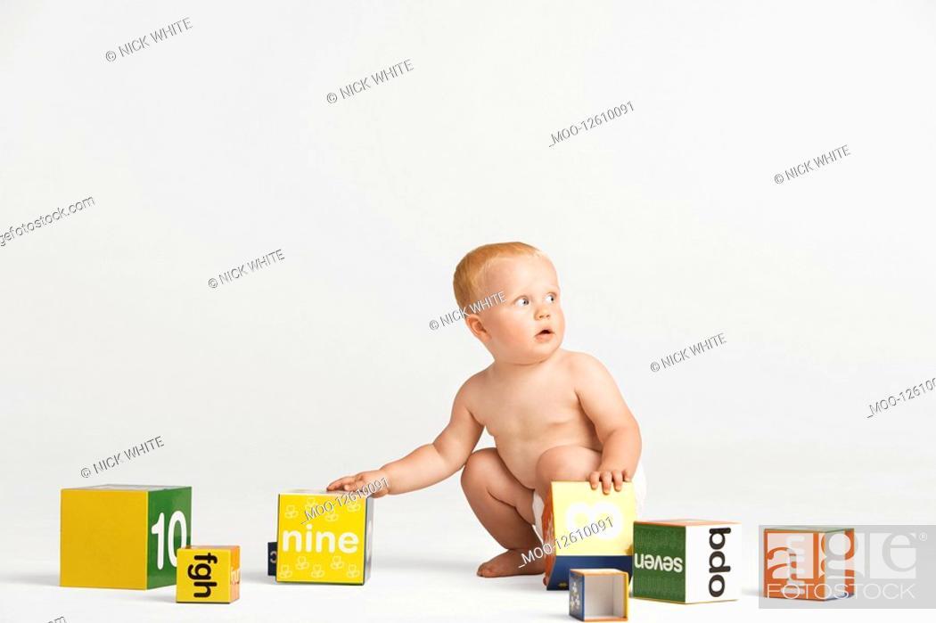 Stock Photo: Baby Picking Up Blocks.