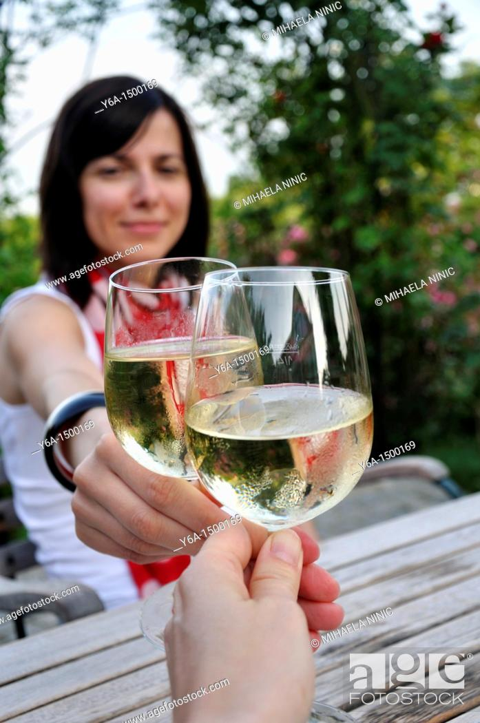 Stock Photo: Young woman clinking glasses with friend in outdoor restaurant.