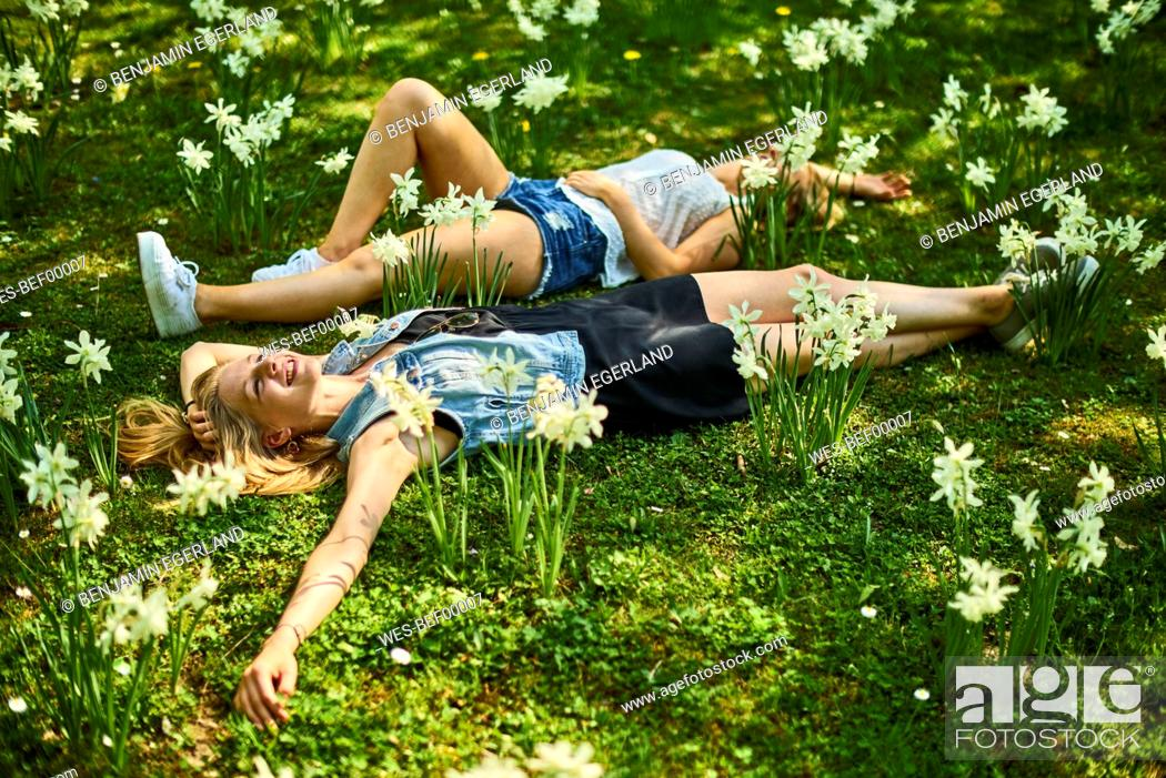 Photo de stock: Two friends relaxing on flower meadow.