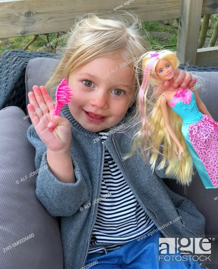 Stock Photo: Little girl, 3 years old, holding a Barbie doll.
