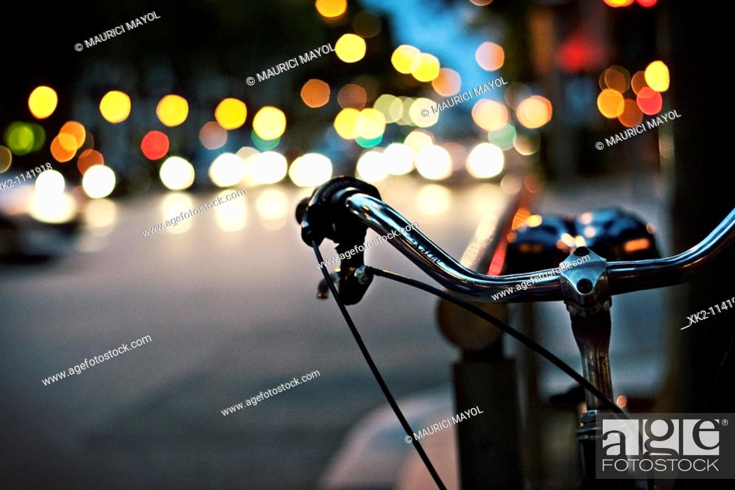 Stock Photo: Handlebar of bike and lights in background, Barcelona, Catalonia, Spain.