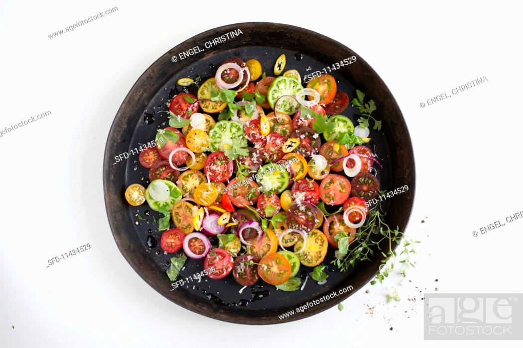Photo de stock: An heirloom tomato salad with onion rings and herbs.