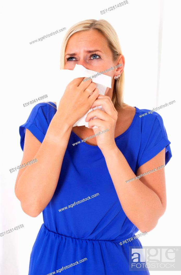Stock Photo: blond woman blowing her nose.