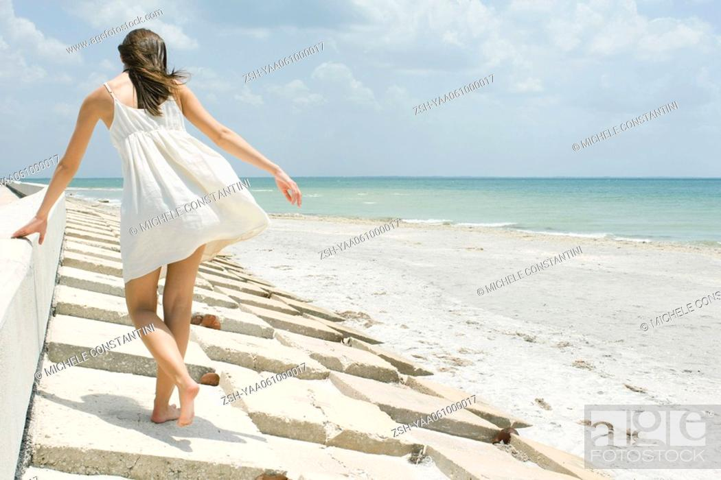 Stock Photo: Young woman walking along low wall at the beach, rear view.