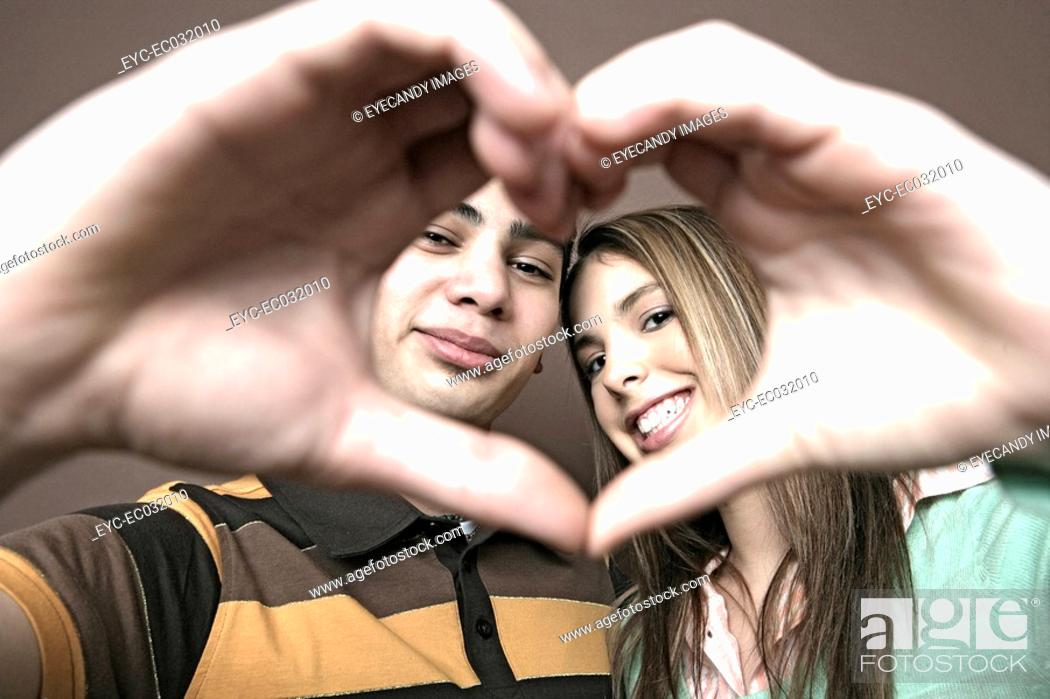 Stock Photo: View of two teenagers shaping a heart.