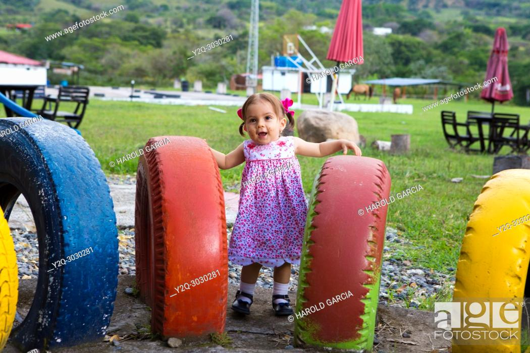 Stock Photo: Baby girl playing in a play ground full of colorful tires.