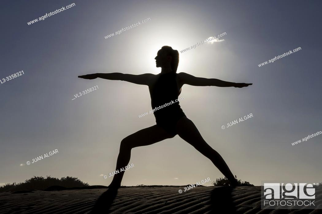 Stock Photo: Silhouette of woman standing in asana on sandy coastline against back lit.